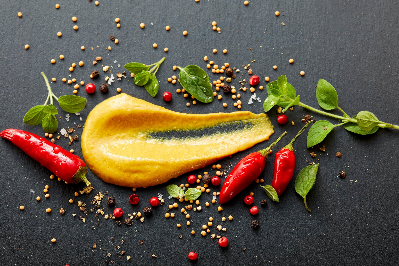 Grillido Chipotle Senf, gelber Senf mit Löffel verstrichen auf schwarzem Hintergrund mit roten Chillis
