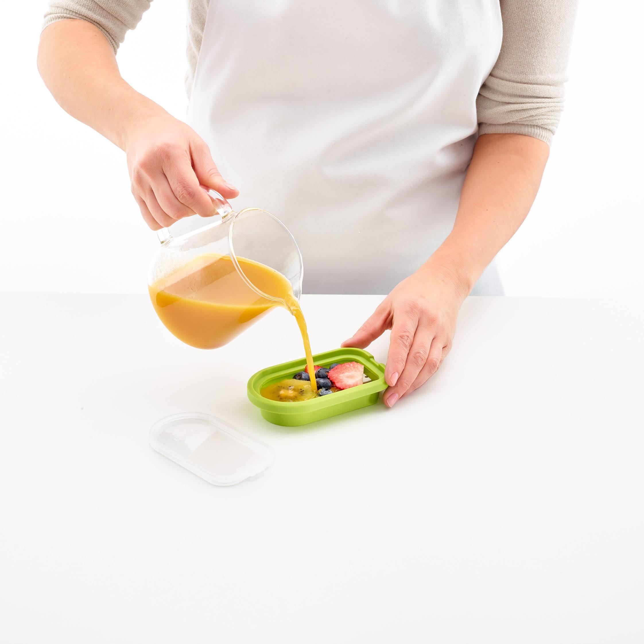 Eisform gefüllt mit Früchten wird mit Saft gefüllt