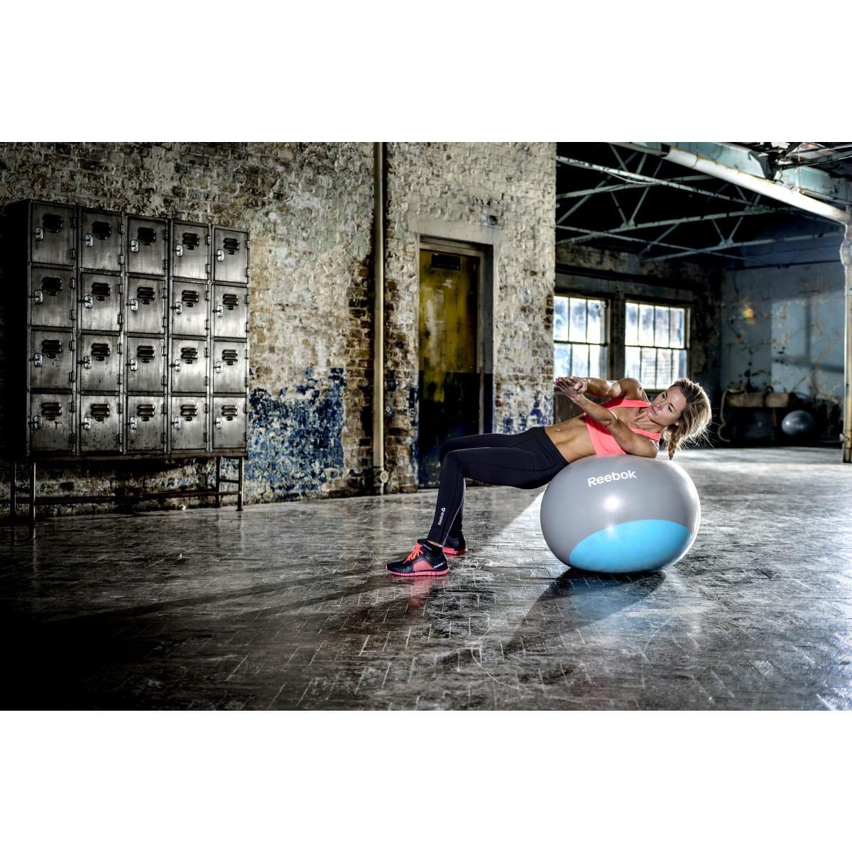 Reebok Ballon de gymnastique, en caoutchouc bleu et gris, femme en plein sport 3